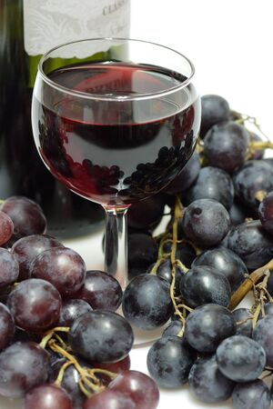 Red wine in a glass with grapes and wine bottle on white background Stock Photo - 3938028
