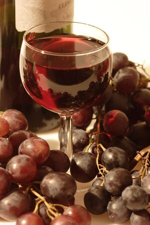 Red wine in a glass with grapes and wine bottle on bright background Stock Photo - 3938019