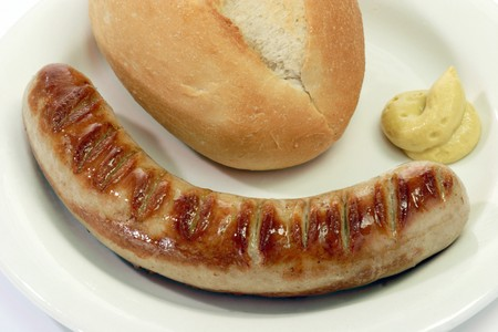 bratwurst: Grilled thuringian bratwurst with bun and mustard on a plate Stock Photo