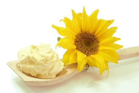 Vegetable oleo on a cooking spoon with sunflower on white background Standard-Bild