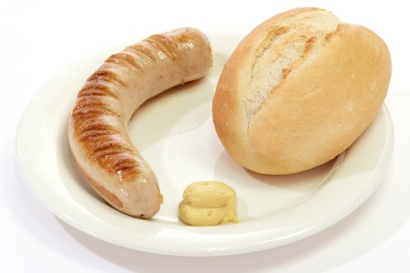 Grilled thuringian bratwurst with bun and mustard on a plate Standard-Bild