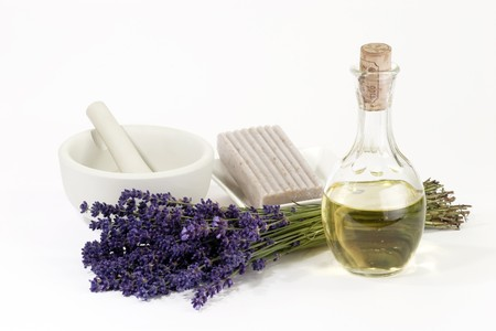 Fresh lavender with mortar, oil bottle and piece of soap on white background