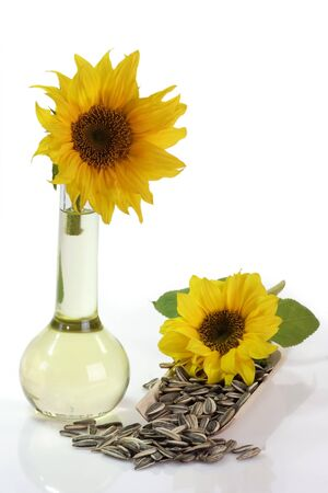 cooking oil: Cooking oil in a plastic bottle with sunflowers and sunflower seeds on white background