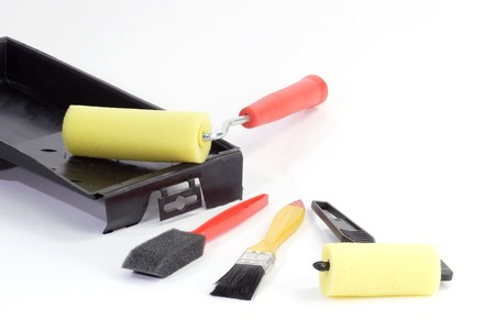 Varnishing assortment with paint-brushes and rollers on bright background