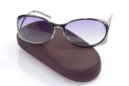 fashon: Trendy sunglasses on brown spectacle case over white background