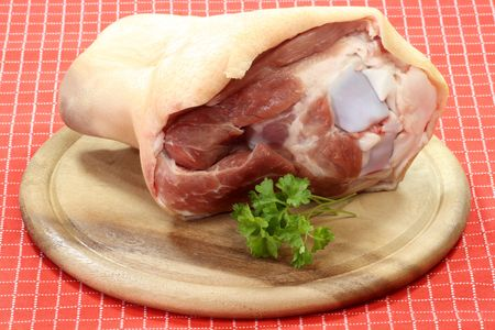 Raw hog-shank on a wooden plate over red background