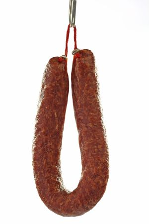 Home-made salami hanging on a hook - isolated over white background Stock Photo