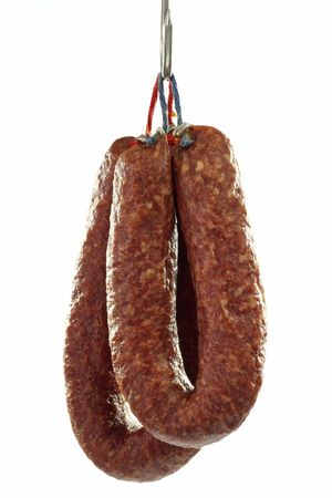 Home-made salami hanging on a hook - isolated over white background Standard-Bild