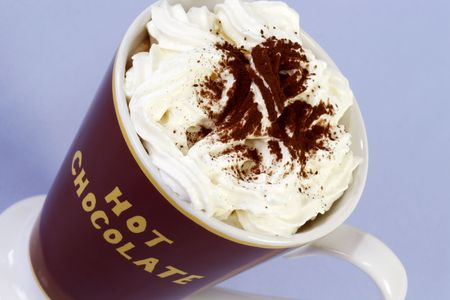 A mug of hot chocolate with whipped cream over light blue background