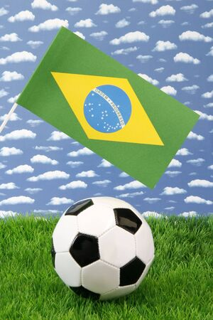 Soccerball on grass with brazilian national flag over sky background photo