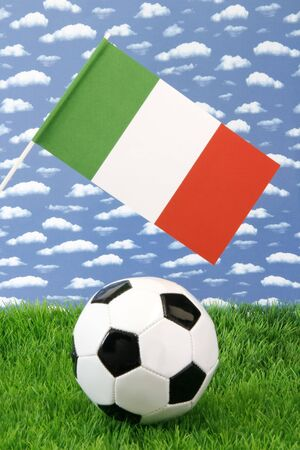 Soccerball on grass with italian national flag over sky background photo