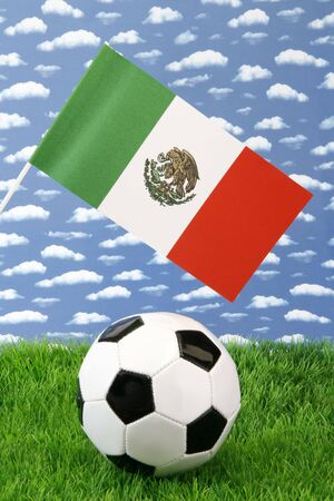 Soccerball on grass with mexican national flag over sky background photo