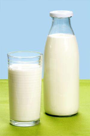 Glass of milk and milkbottle over blue background