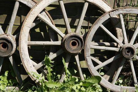 old wood farm wagon: Close-up of three ancient cartwheels on a farm