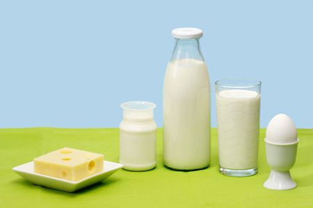 Fresh milk, yogurt, cheese and egg over blue background