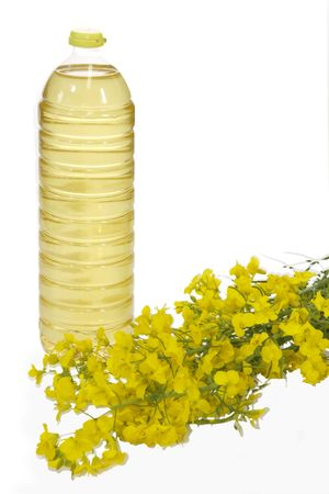 Colza oil in a plastic bottle with yellow blooming rape - isolated on white Stock Photo