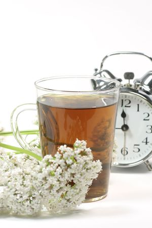 sleep disorder: Herbal tea in a glass with valerian blossoms and alarm clock over white background Stock Photo