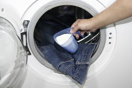 Close-up of a hand holding a filled cup of washing powder in front of a washing machine