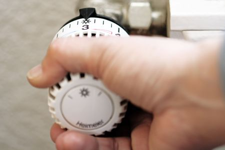 regulating: Hand regulating temperature with a thermostat