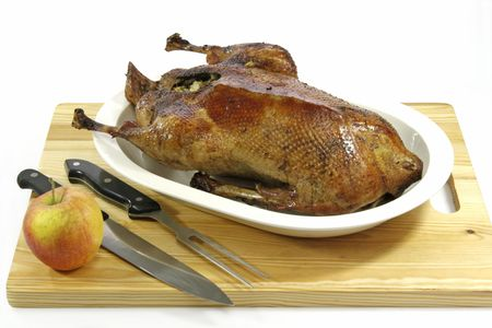 Crunchy roasted goose stuffed with apples on a plate Stock Photo