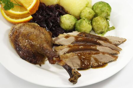 Goose breast and thigh with sides on a plate