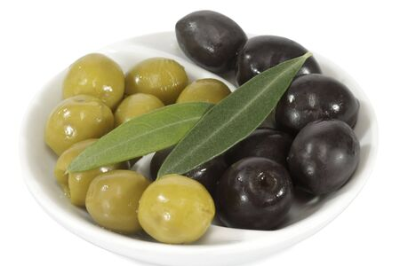 Black and green olives with leaves over white background