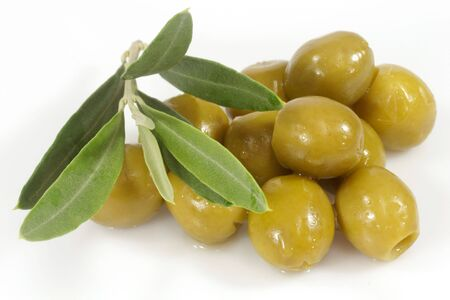 Green olives with olive branch on white background Stock Photo