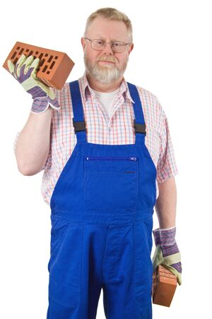 Bricklayer in blue overalls holding bricks in his hands - isolated on white