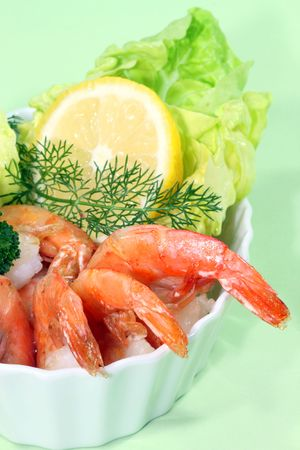 Cooked shrimps with lemon and lettuce in a bowl