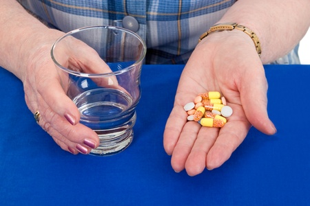 Elderly woman holding pills and a glass of water Stock Photo