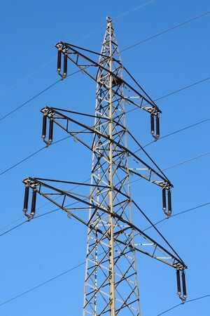 Electricity pylon against blue sky photo