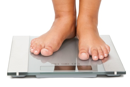 Young woman standing on bathroom scales Stock Photo