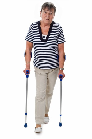Senior woman with crutches - isolated on white