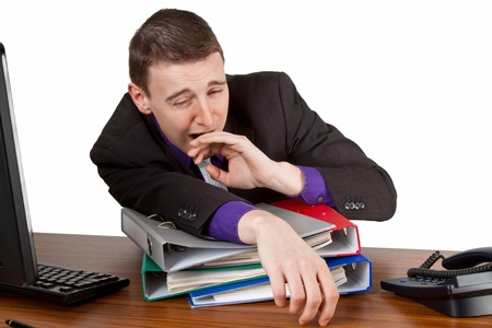 Young businessman yawning at his desktop - isolated