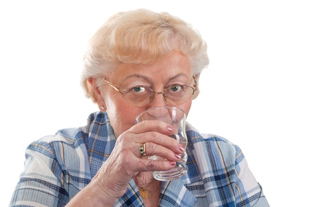 Elderly woman drinking a glass of water - isolated Stock Photo