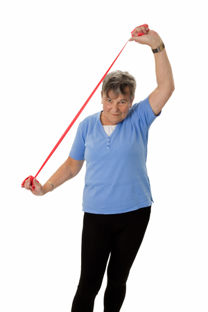 rubberband: Mujer mayor que ejercita con la goma - aislado Foto de archivo