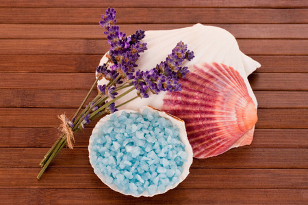 bath salts: Blue bath salts with lavender blossoms over wooden background