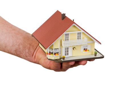 Male hand holding a model house - isolated photo