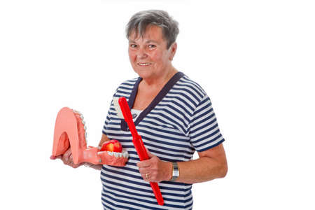 dentition: Senior woman with dentures, apple and toothbrush - isolated