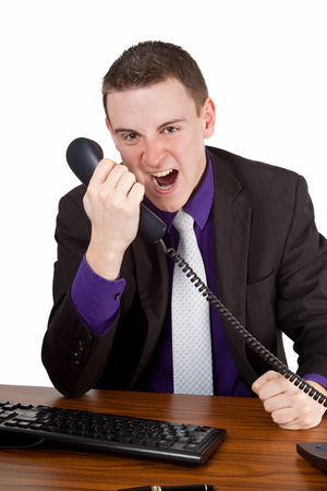 Young businessman screaming into telephone - isolated photo