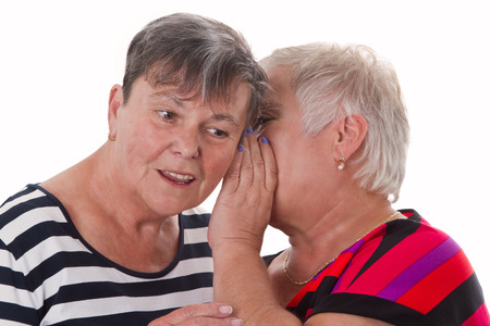 Two senior women whispering - isolated