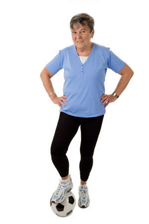 Sportive senior woman with football - isolated