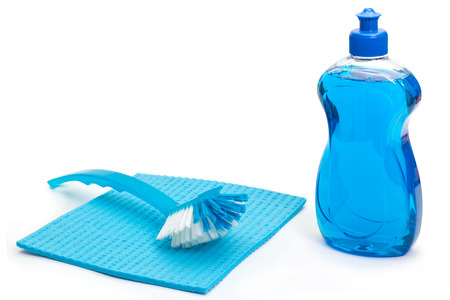 Blue dishwashing detergent with brush and cloth on white background