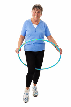 senior woman exercising: Senior woman exercising with hula-hoop - isolated