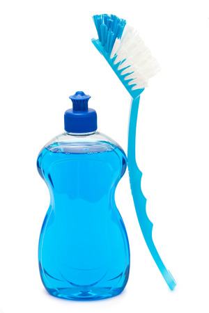 Dishwashing detergent with dishwashing brush over white background