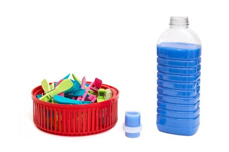 clothespegs: Bottle of blue laundry detergent near clothespins in a basket