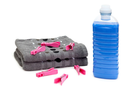 clothespins: Bottle of blue laundry detergent near stack of towels with clothespins