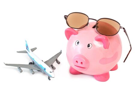 holiday budget: Piggy bank with sunglasses and toy plane on white background