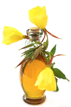 Evening primroses with oil bottle on white background