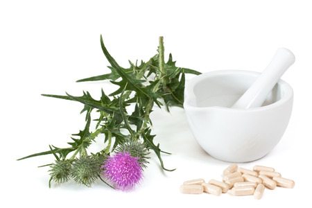 Milk thistle and capsules near mortar and pestle on white background Standard-Bild